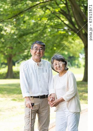 公園を散歩してリハビリをするシニアのカップル 67615871