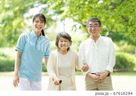 公園を歩くシニアのカップルと介護士 67616294