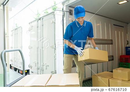 トラックに荷物を積みこむセールスドライバーの女性 67616710