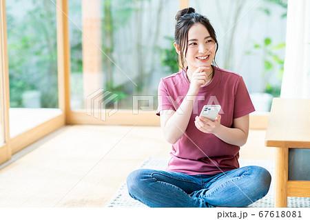 リビングでスマホを操作する若い女性 67618081