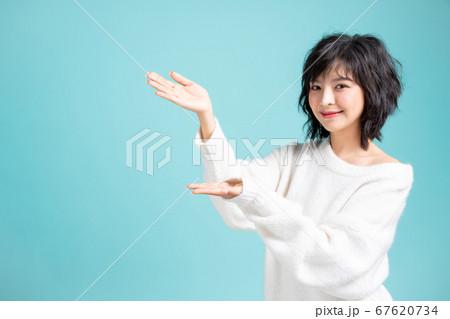両手で案内紹介ポーズをする若い可愛い女性モデル 67620734