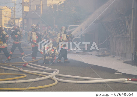 煙に巻かれながら消火活動をおこなう消防士 67640054
