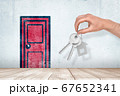 Hand holding silver keys with red cartoon door drawn on white wall background 67652341