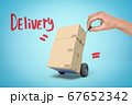 Hand holding tiny hand truck with cardboard boxes and 'Delivery' sign on blue background 67652342