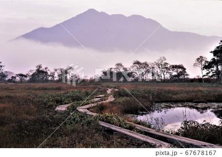 草紅葉が始まった壮大な湿原 早朝の燧ヶ岳と朝霧を背景に、曲がりくねった木道と沼地 67678167
