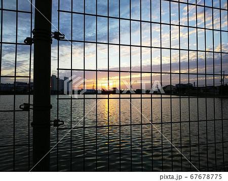 フェンス越しに見える水面に写る変わりゆく秋の空色と夕暮れの太陽 67678775