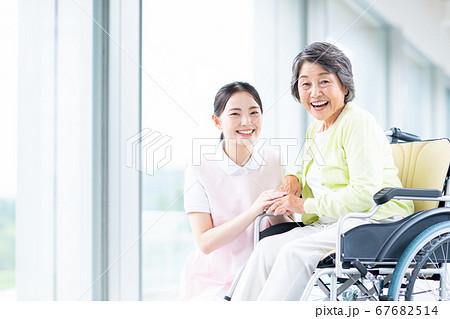 車椅子のシニアの女性と介護スタッフ 67682514