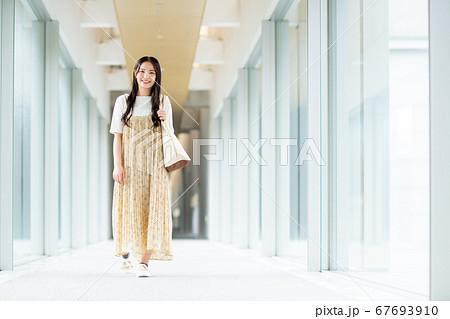大学構内の廊下を歩く若い女性 67693910