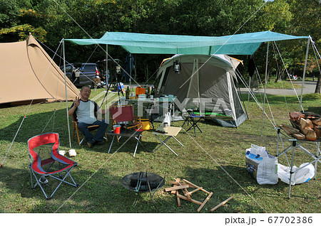 秋キャンプを楽しむ男性ソロキャンパー 67702386
