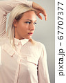 Pensive beautiful female blonde model in shirt looking away from camera 67707377