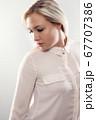 Pensive beautiful female blonde model in shirt looking away from camera 67707386