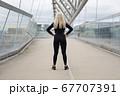 Back of fit blonde woman runner standing on bridge in modern looking city 67707391