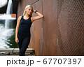 Beautiful Fit Woman in Sportswear Leaning On Metallic Wall After Workout 67707397