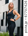 Confident Fitness Woman in Workout Outfit Standing in Futuristic Modern City 67707426