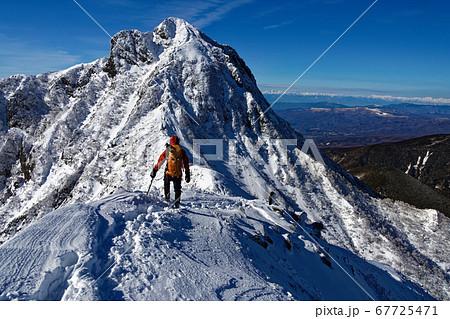 八ヶ岳連峰・中岳稜線を行く登山者と阿弥陀岳・北アルプスの眺め 67725471