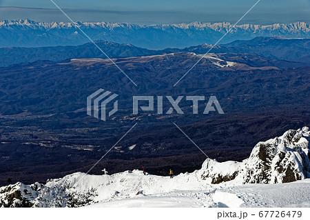 八ヶ岳連峰・阿弥陀岳から見る御小屋尾根を行く登山者と北アルプスの山並み 67726479