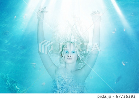 Young blond woman floating in the depths of a blue 67736393