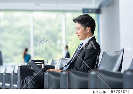 空港 ビジネスマン パソコンを使うミドルビジネスマン 67737876