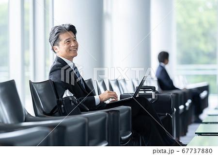 空港 ビジネスマン パソコンを使うミドルビジネスマン 67737880