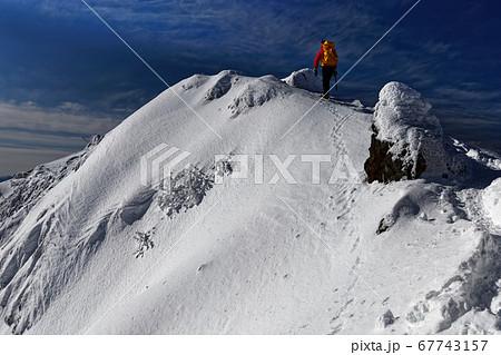 厳冬の八ヶ岳連峰・赤岳山頂を行く登山者 67743157