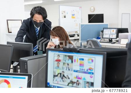 web会議 画面越しの会社にいるマスクをつけた会社員2人 67778921