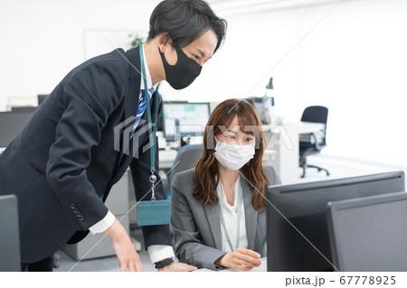 マスクをつけて仕事をする会社員2人 67778925