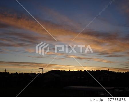 雲が色づく朝焼けの空と逆光で黒く見える山 67783878