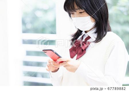 マスクをしてスマホを見る女子高生 67789882