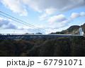 青空と山々に囲まれた大自然のなかに架かる吊橋 67791071