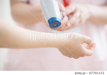 医療 非接触体温計で検温する看護師(手元) 67791152