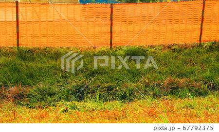 オレンジ色のフェンスネットで囲われた工事現場の風景 67792375