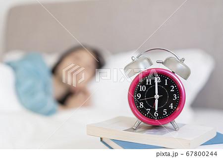 睡眠中の女性のそばに置かれた目覚まし時計 67800244