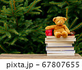 Little teddy bear toy and books on wooden table 67807655