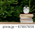 vintage alarm clock and books on wooden table with 67807656