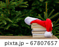 Santa Claus hat and books on wooden table with 67807657