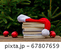 Santa Claus hat and books on wooden table with 67807659