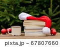 Cup of coffee and books with Santa Claus hat on 67807660