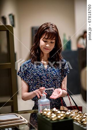 店内で手を消毒するショッピング中の女性 67818760