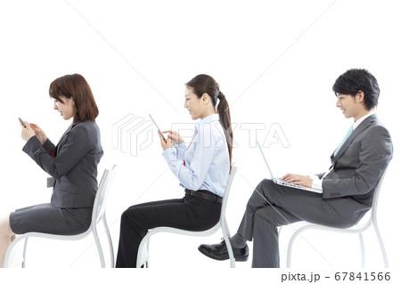 モバイル機器を操作するビジネスマンとOL 67841566