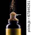 Jar of chocolate protein with scoop and falling powder isolated on black 67846261