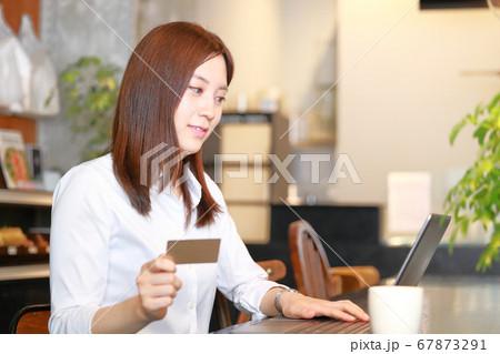 カフェでクレジットカードで買い物を楽しむ女性 67873291