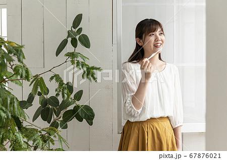 窓際で外を見ながら歯磨きする若い女性 67876021