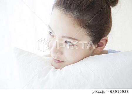 枕を抱きしめる女性 67910988
