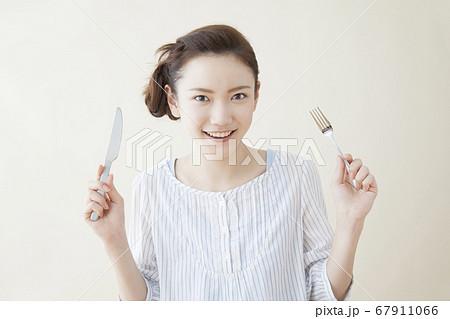 ナイフとフォークを持つ女性 67911066