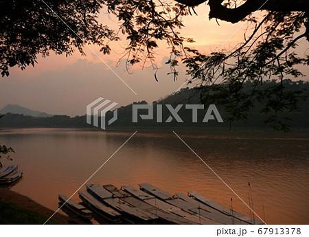 ラオスの世界遺産の町、ルアンパバーンのメコン川沿いから見る夕暮れ時の風景 67913378