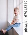 Adorable little girl sits the windowsill in studio 67918240