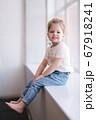 Adorable little girl sits the windowsill in studio 67918241