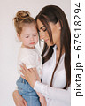 Portrait of Little girl with mom in studio. White background 67918294