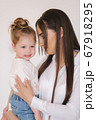 Portrait of Little girl with mom in studio. White background 67918295