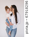 Portrait of Little girl with mom in studio. White background 67918296